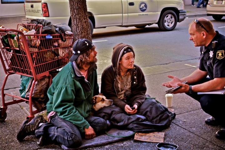 "A police officer speaks with a ""family"" of homeless youth in Berkeley in 2013. Photo: Ted Friedman"