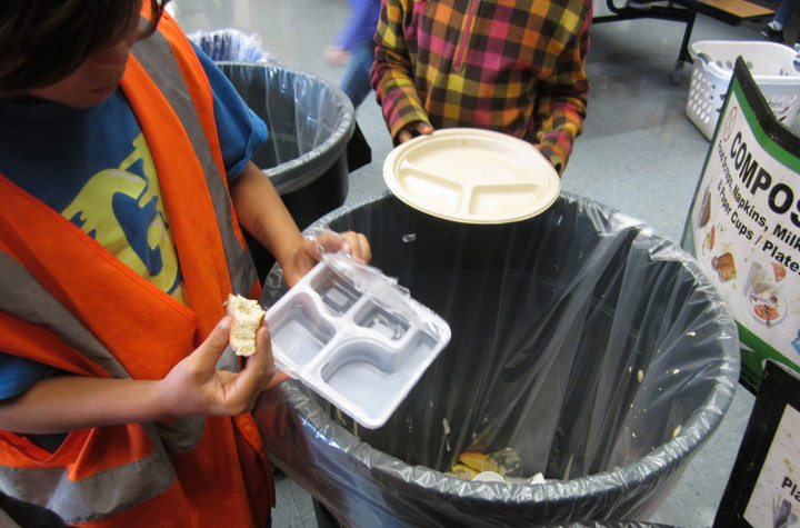 A third-grade monitor at Oxford Elementary helps a classmate figure out what gets composted and what goes into the trash. Photo: Green Schools Initiative