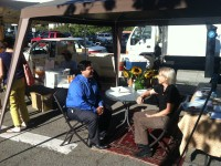 Councilman Jesse Arreguin talks with a local woman at North Berkeley Farmers Market. Photo: Anthony Sanchez.