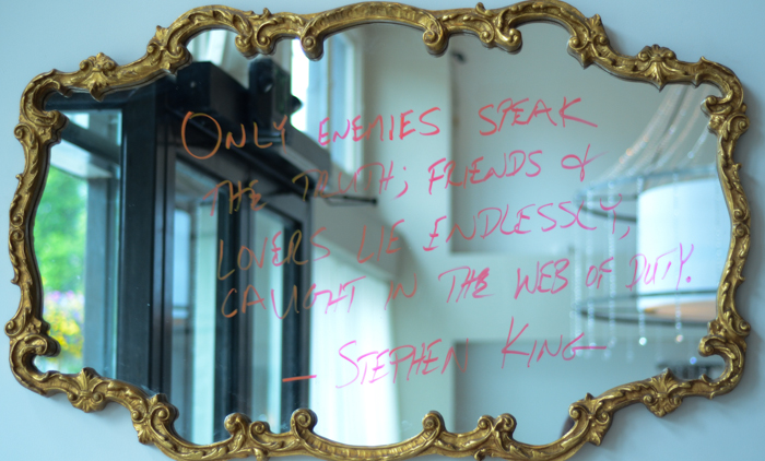 A mirror hung on the wall just as you walk in reads: