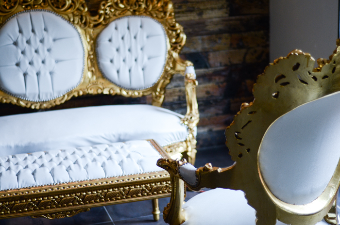 """Ornate golden and white furniture in the back section of the restaurant, an area designed for lounging called """"The Throne Room""""."""