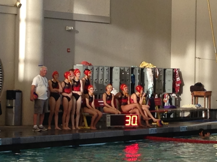 Bill Gaebler, BHS swimming and water polo coach, stands next to the freshmen girl's water polo team at a meet. Photo: Marilee Enge