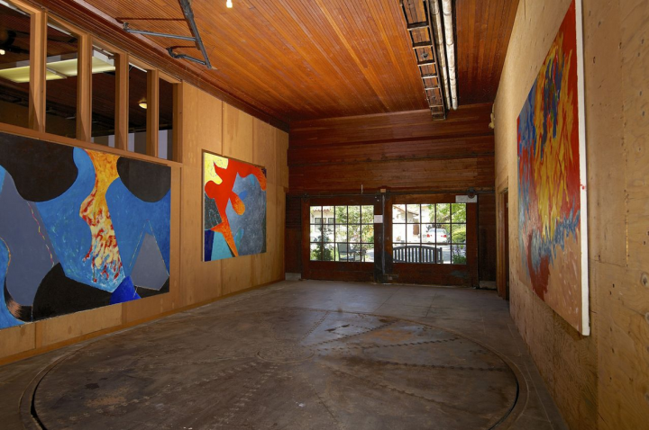 The home comes with its original ball-bearing turntable which meant chauffeurs did not have to reverse out the garage space, seen here with some artworks by the artists who lived in the house most recently. Photo: Holly Rose Homes