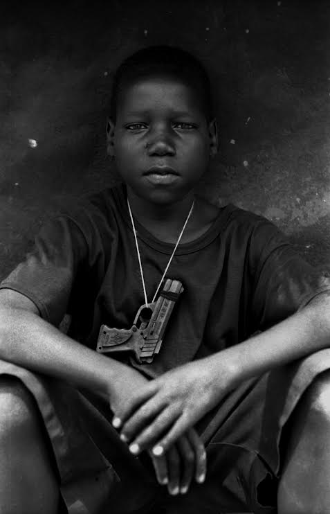 Acholi boy with toy gun, Muchwini Internally Displaced Camp, Uganda. Photo: Thomas Morley