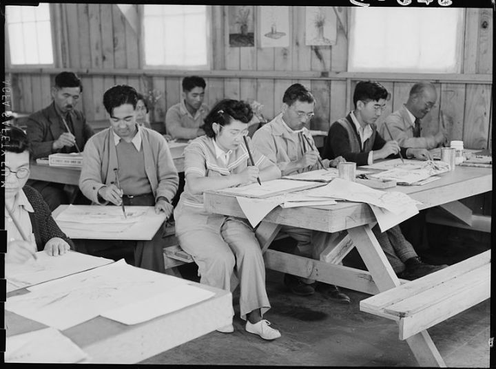 San Bruno, California. An art school has been established at this Assembly center with a well trained, experienced evacuee staff under the leadership of Professor Chiura Obata, who before evacuation was an associate professor of art at the University of California. This photograph shows part of the morning class learning free hand brush strokes. Photo: Department of the Interior/Wikimedia