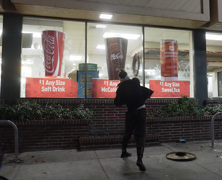 A protester flings a garbage can lid through a window at a McDonald's restaurant during a vandalism spree downtown while protesting police brutality in Berkeley, late Sunday, December 7, 2014. People marched through the streets of Berkeley for the second night in a row Sunday to protest the recent decisions by grand juries in Ferguson, Mo., and New York to not indict white police officers in the deaths of two unarmed black men. Photo: David Yee ©2014