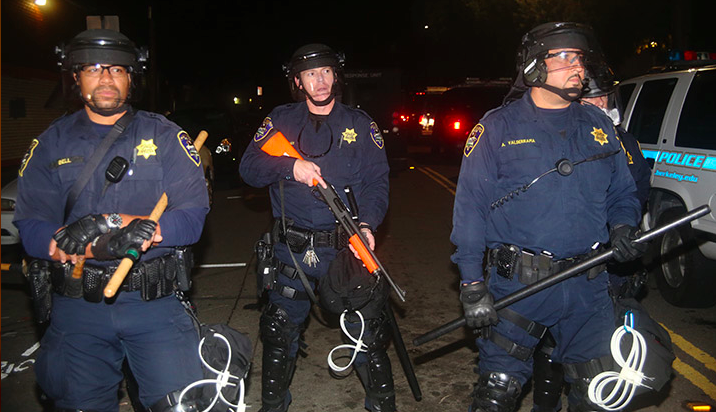 Police in riot gear form a line at University Avenue and Acton Street against protesters marching against recent grand jury decisions against indicting police officers for killing unarmed black men, in Berkeley, on Saturday, December 6, 2014. Photo: David Yee ©2014