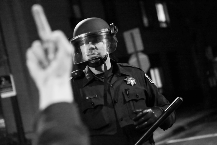 A protester gives the finger to a police officer during a protest that started in Berkeley on Sunday Dec. 7, 2014. Photo: Kelly Owen