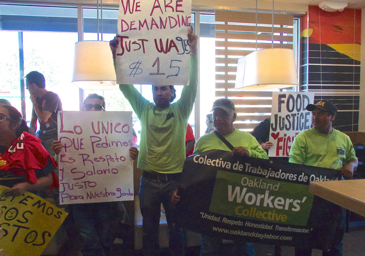 Protesters hold up signs in the McDonald's in Oakland's Temescal neighborhood. Photo: Ted Friedman