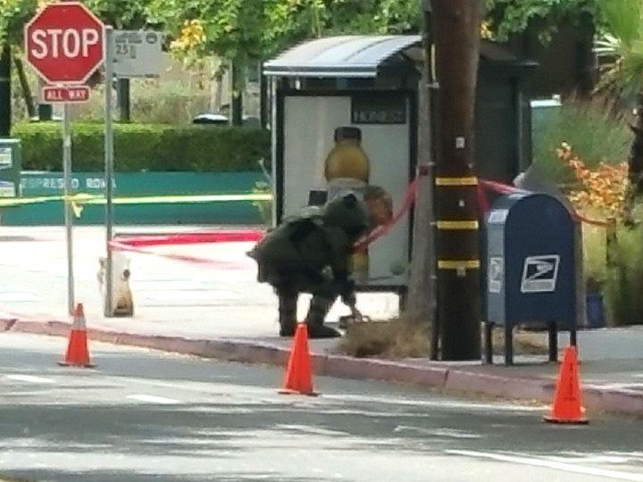 A bomb squad member bends down to look at a suspicious package under investigation in North Berkeley. Photo: Devin Taylor-McDonald