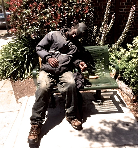 A man asleep on a bench, or sculpture? Photo: John Harris