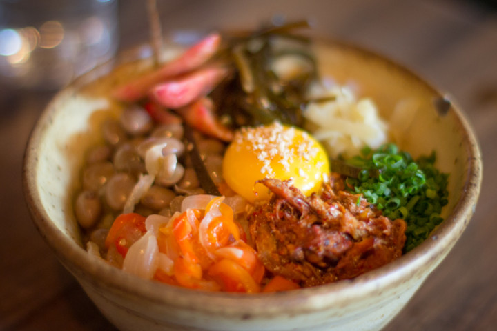 Pulled pork donburi ($13.50) with Hen Pen Farms raw egg yolk, pickled ginger, kombu, scallions, cranberry beans, peperonata, and smashed French breakfast radishes at Ramen Shop. Photo: Benjamin Seto