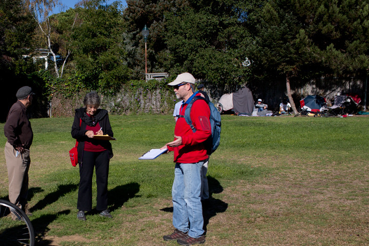 Maio walked through Ohlone Park with more than a dozen neighbors on a recent Saturday to identify problem areas in the park. In the background, a cluster of tents. Photo: Emilie Raguso