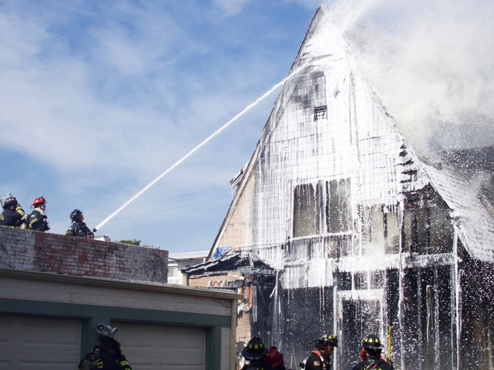 Firefighters shoot water at the house fire on Haste in Berkeley between Shattuck and Fulton. Photo: Ted Friedman