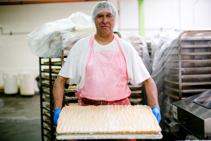 A worker with cake at Rubicon Bakers. Photo: Clara Rice