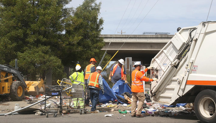 A Berkeley public works crew clears out a homeless encampment near the Gilman Street offramp of I-80, in Berkeley, on Thursday, June 16, 2016. Photo: David Yee