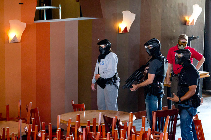 "In one drill, police respond to a ""bar"" in which a woman with a sword is having a mental health crisis. (The helmets they are wearing are safety gear due to the type of rounds used in the training exercise.) Photo: Emilie Raguso"
