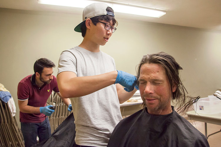 Chris Ki, an undergraduate at UC Berkeley, cuts the hair of Michael Georgeius, a client of The Suitcase Clinic. Photo: Brittany Hosea-Small/UC Berkeley
