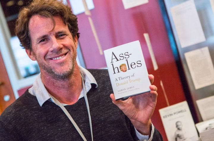 Aaron James holding up a his book Assholes: A Theory of Donald Trump after signing copies at the Books Inc. popup bookstore at Uncharted. Photo: Kelly Owen