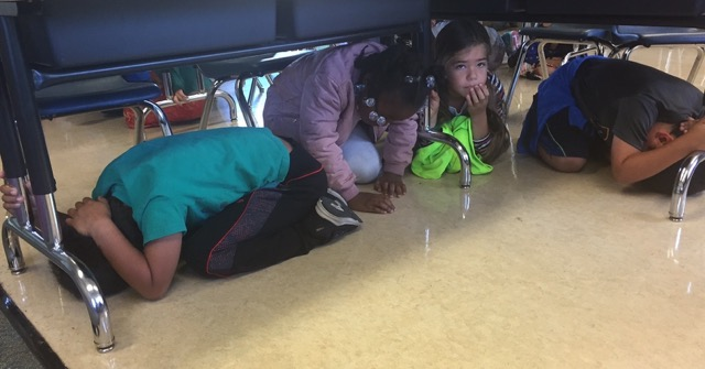 """Kids at LeConte Elementary School practice their """"Drop, cover, and hold"""" technique during the Great Shakeout. Photo: Daphne White"""