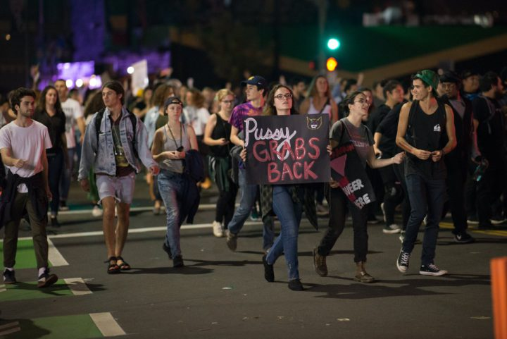 """A protester holds a """"Pussy grabs back"""" sign after Donald Trump was elected president Tuesday. Photo: Daniel McPartlan"""