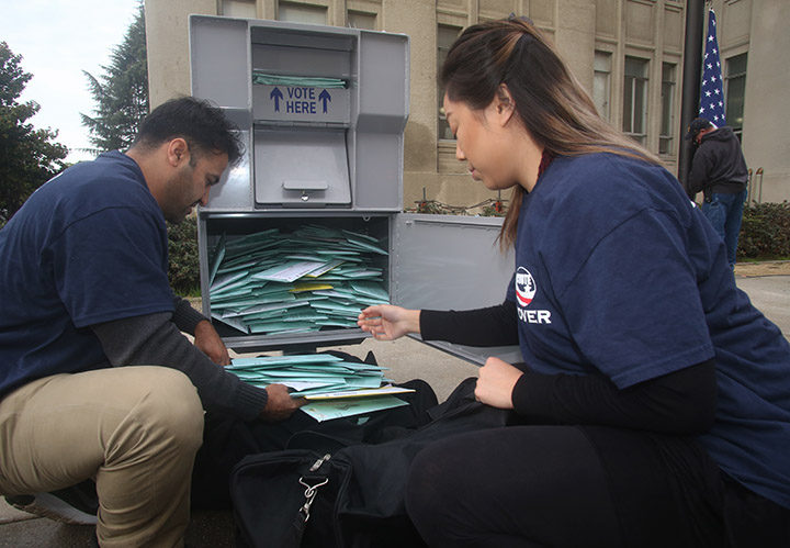 Alameda County Registrar of Voters employees Mohammad Naweedyamin, left, and Michelle Lin, collect vote-by-mail ballots from a full drop box at City Hall, in Berkeley, on Monday, Nov. 7, 2016. The drop boxes are emptied twice a day, Lin said. Photo: David Yee ©2016