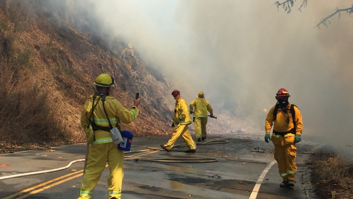Firefighters on road with smoke in the background
