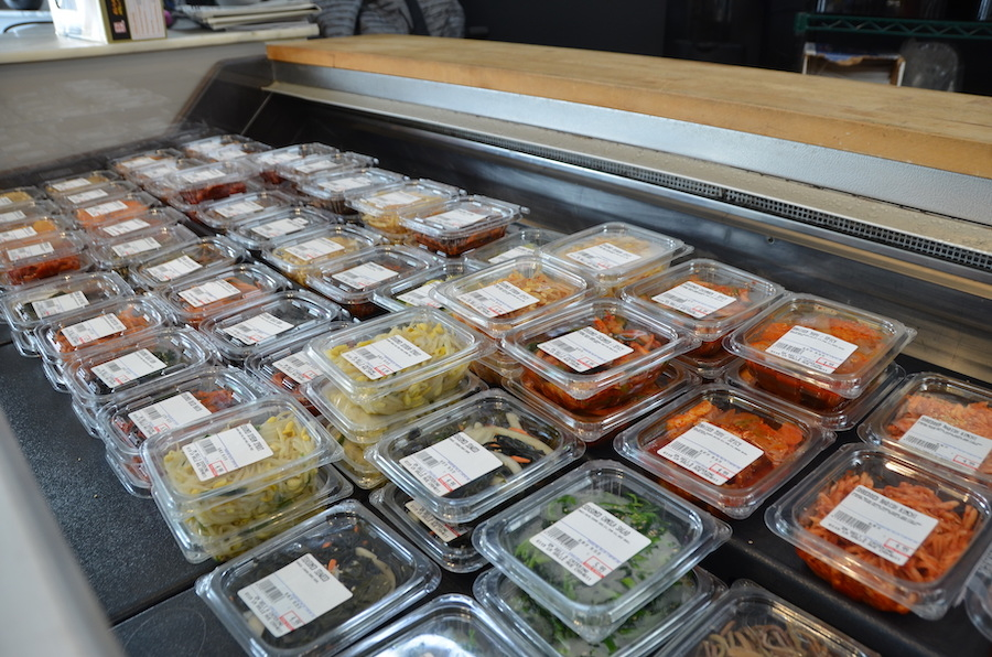 Em Deli & Catering's refrigerator case filled with prepared Korean side dishes
