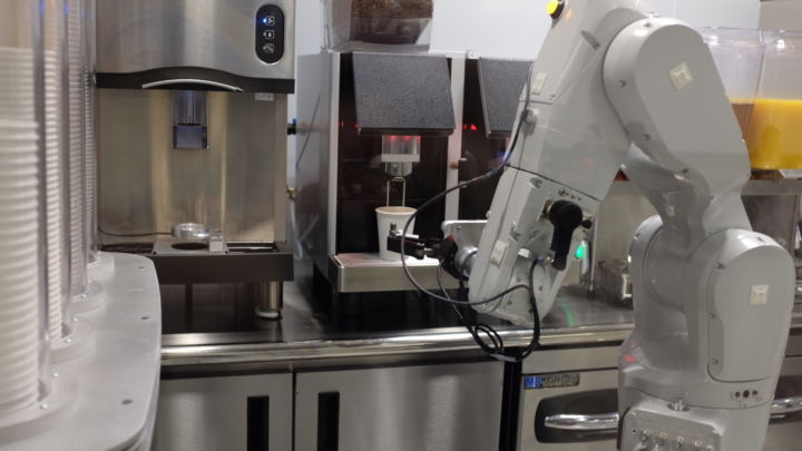 A robotic arm holds a coffee cup underneath a drink dispenser