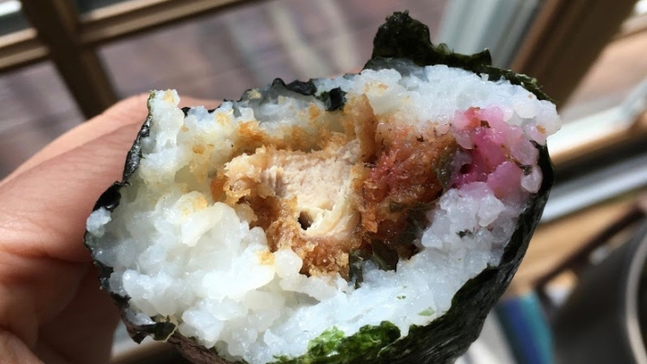 A hand holding an onigiri filled with fried chicken katsu and purple ume-shiso filling in front of a window.