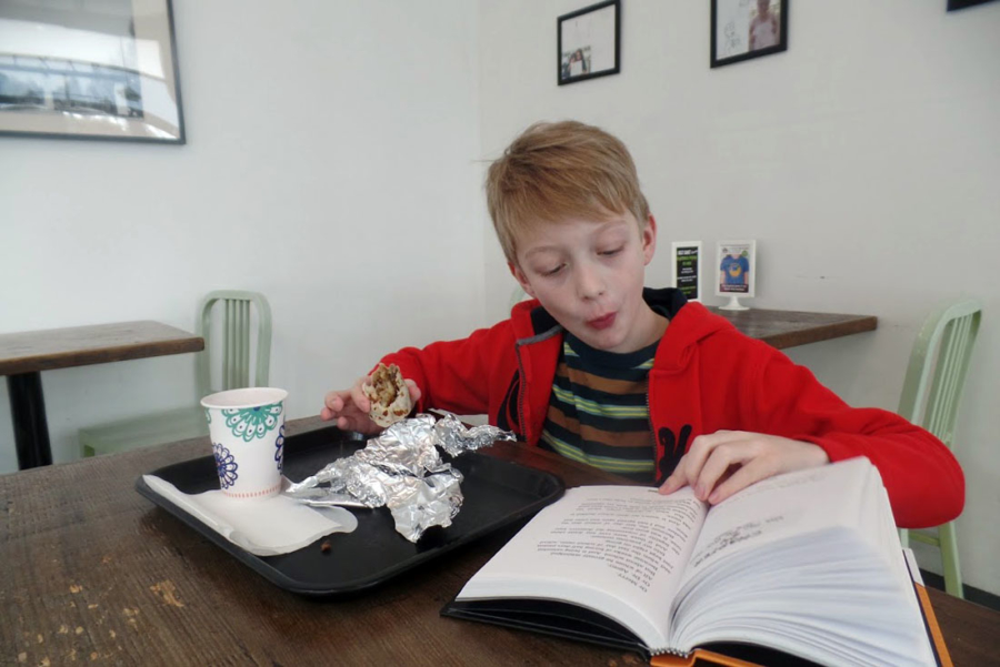 An 8-year-old boy sits at a table reading a book and eating a burrito at Best Coast Burritos in Emeryville.
