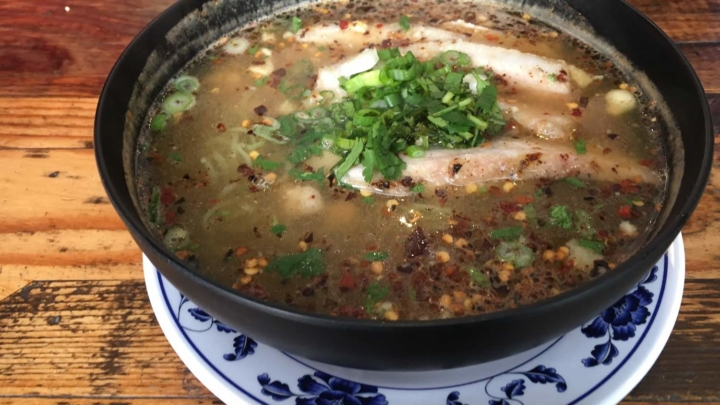 A bowl of Tom Yum Noodle soup topped with pork jowl strips, green onions and cilantro from Bird & Buffalo Thai restaurant in Temescal, Oakland.