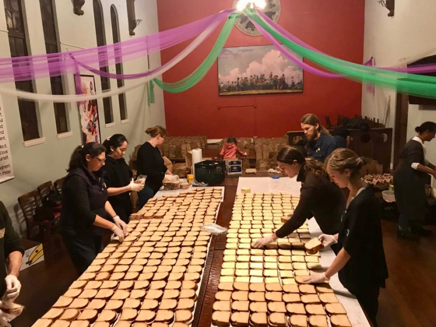 People stand around a table covered by slices of bread, preparing sandwiches to distribute to students during the Oakland teachers strike.