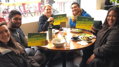 Five teachers sit around a round table at Farley's East holding signs supporting teachers on strike in Oakland.