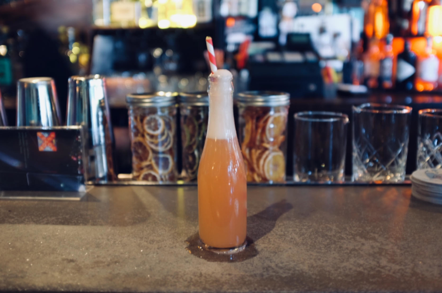 A glass bottle filled with a foamy orange cocktail with a red and white stripe straw sticking out of it sits on a bar at the Hotsy Totsy Club in Albany.