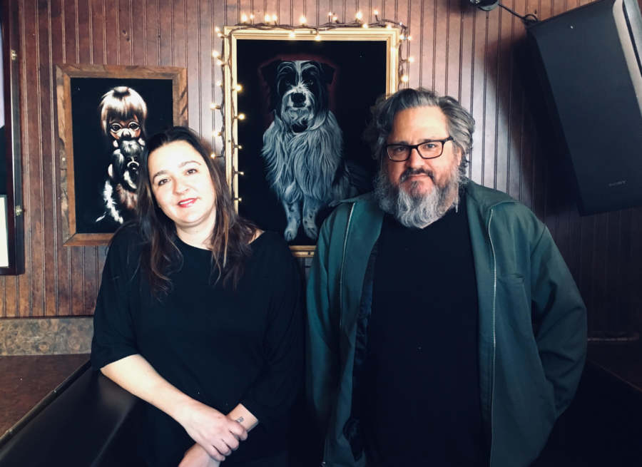 A man and woman stand in front of a wall with two hanging velvet paintings at The Hotsy Totsy Club in Albany.