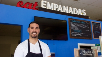 """Chef-owner Javier Sandes stands in front of lighted signage that says """"eat empanadas"""" and a menu of the offerings at Javi's Cooking in West Oakland."""