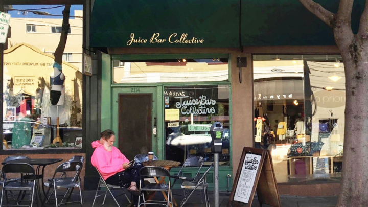 A man in a pink hoodie sits on outdoor seating in front of the Juice Bar Collective in Berkeley.