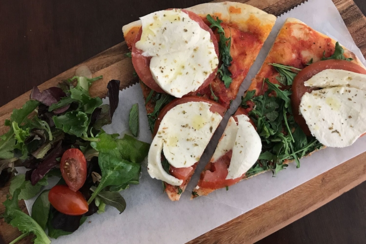 A side salad and two slices of pizza topped with mozzarella, tomato and arugula.