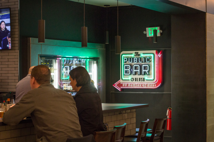 "Two people sit at a bar in front of a neon sign that says ""The Public Bar by Blush: 99 Bottles of Beer"""