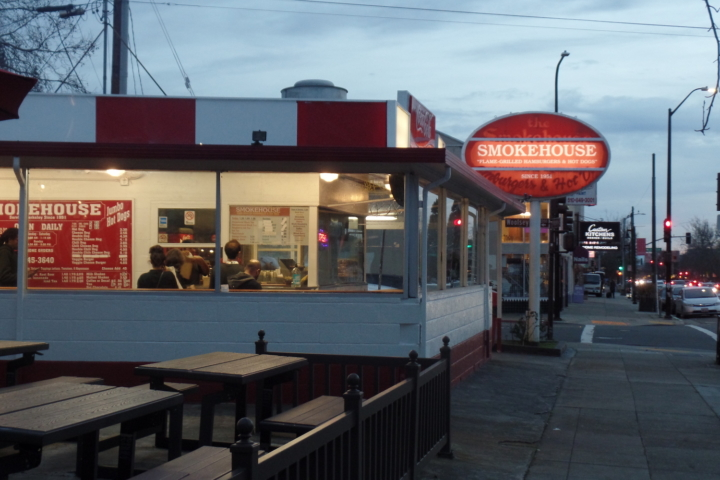 Outdoor picnic tables in front of a lit-up restaurant. A glowing sign in the background reads Smokehouse