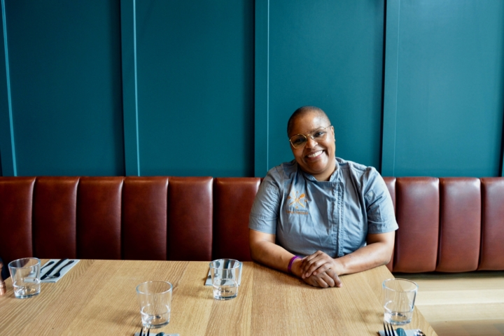 Tanya Holland sits at a table at a red banquette in front of a blue wall at Brown Sugar Kitchen in Uptown Oakland.