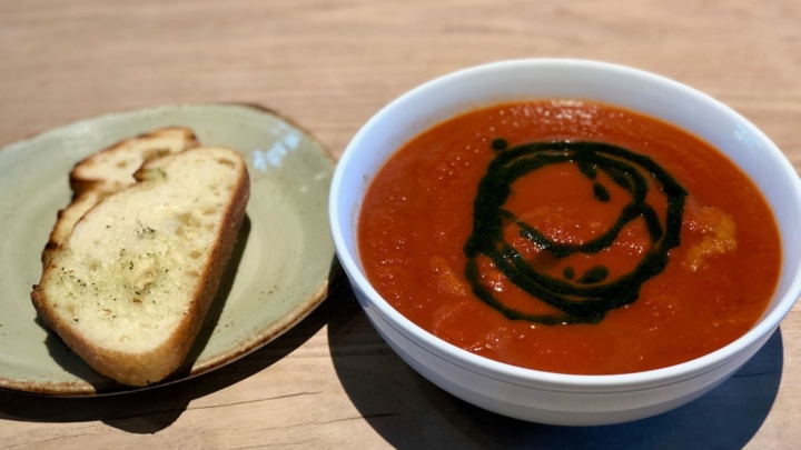 A bowl of roasted tomato soup with basil oil garnish and a side of bread from Tender Greens in Berkeley.