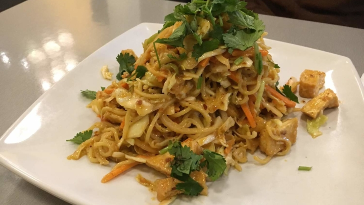 A plate of Rainbow Salad, a Burmese dish of sauced noodles, vegetables and papaya, garnished with cilantro.