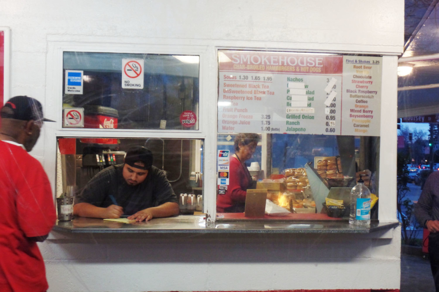 A man at the takeout window takes an order from a customer while a woman cooks burgers in the distance at The Smokehouse in Berkeley.