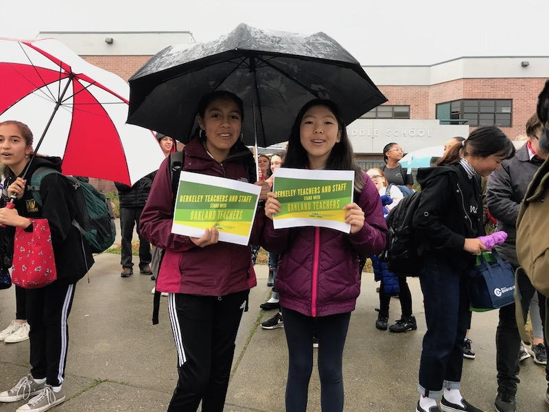 Two female middle school students stand under a shared umbrella holding signs in support of Oakland teachers
