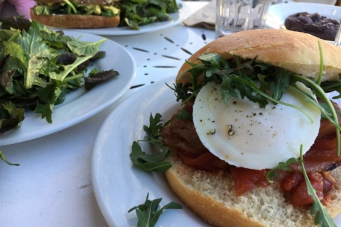 The poached egg sandwich, a side salad, and a curried chicken sandwich in the distance at Baker & Commons in Berkeley.