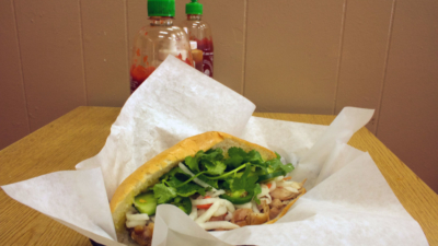 A Vietnamese roasted chicken sandwich sits in a paper lined basket on a table with bottles of sriracha in the distance.