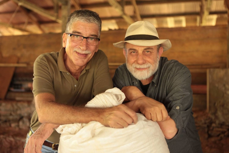 Chocolate maker Claudio Corallo stands with Alegio founder Panos Panagos over a large filled white cloth bag.