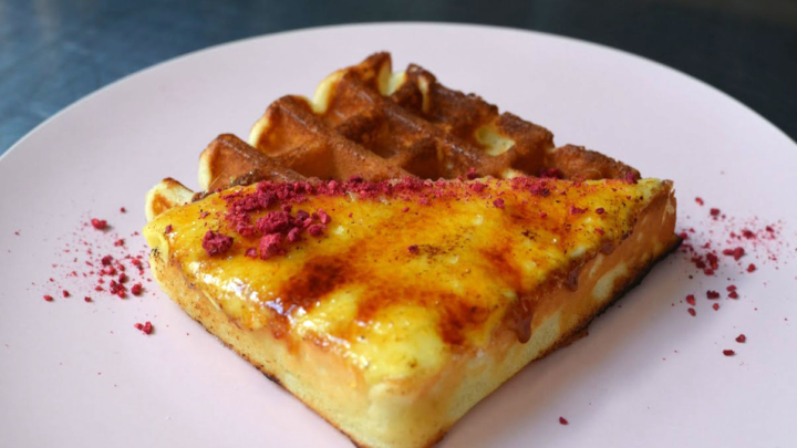 A pink plate featuring a waffle topped with French-style pastry creme and a hardened sugar shell and freeze-dried raspberry crumbles, from Berkeley's Third Culture Bakery